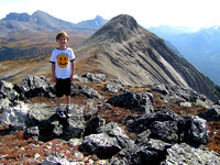 Riley looks proud as he stands atop the west summit. The east peak is to the right of him.